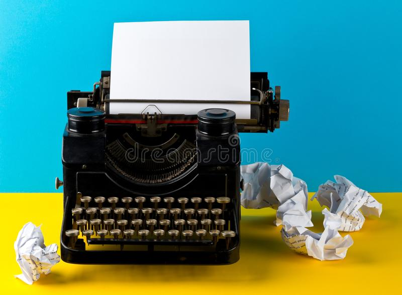 Vintage typewriter with empty, blank sheet of paper and crumbled stock images