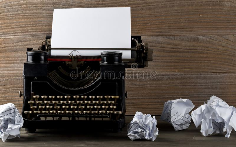 Vintage typewriter with empty, blank sheet of paper and crumbled. Paper balls on wood table background stock photos