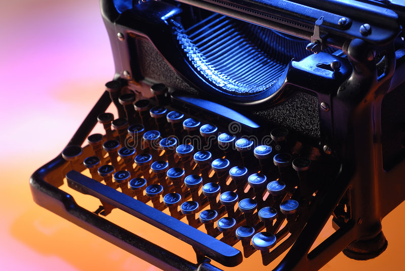 Vintage typewriter front. Old typewriter shot from 3/4 front, lit with blue, orange and magenta lights royalty free stock photography