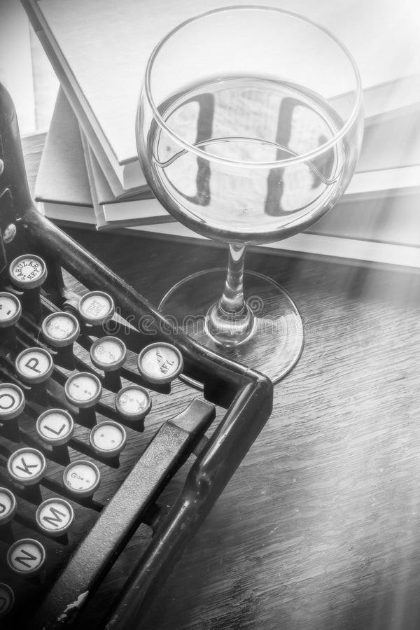 Vintage Typewriter Glass of Wine. Old vintage typewriter with glass of wine pencils and books in this retro creative writing and relazation themed desk top stock photos
