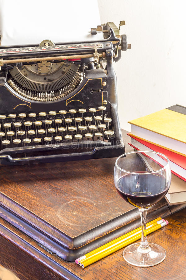 Vintage Typewriter Glass of Wine. Old vintage typewriter with glass of wine pencils and books in this retro creative writing and relazation themed desk top stock image