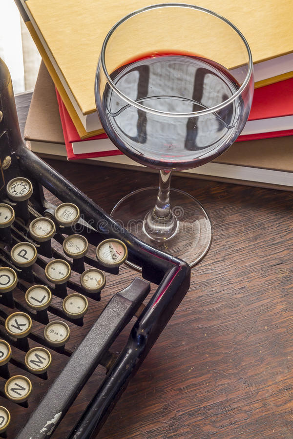 Vintage Typewriter Glass of Wine. Old vintage typewriter with glass of wine pencils and books in this retro creative writing and relazation themed desk top royalty free stock images