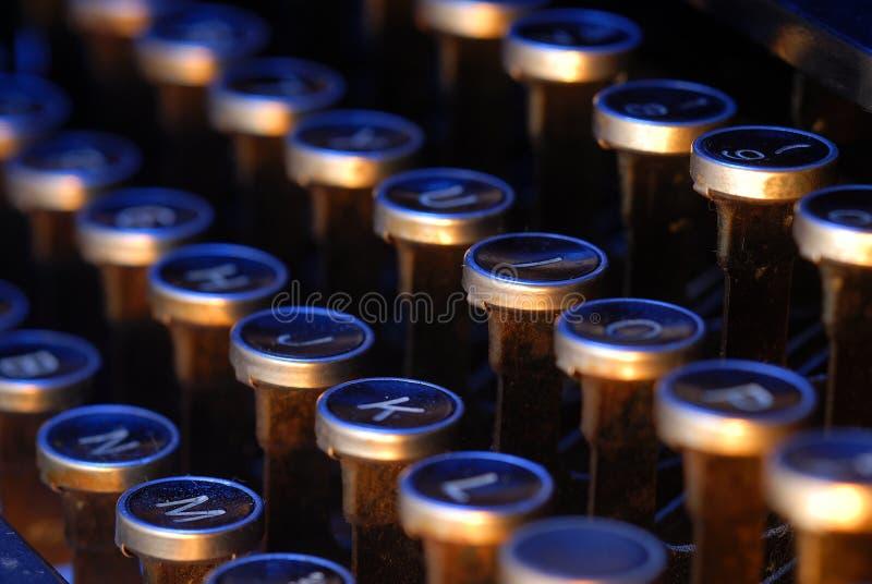 Vintage typewriter keys. Old keys from a vintage typewriter lit with orange and blue lights stock photo