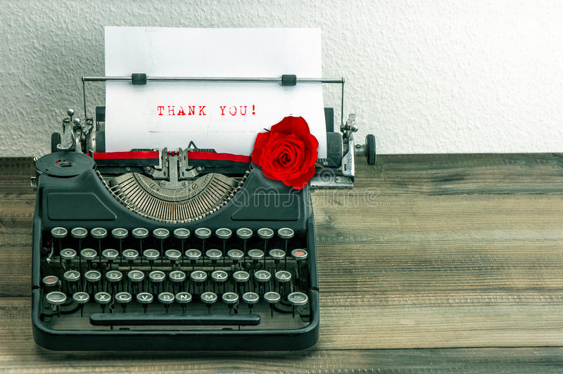 Vintage typewriter with paper page and rose flower stock image