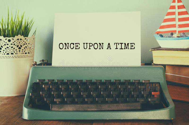 Vintage typewriter with phrase: ONCE UPON A TIME. Photo of vintage typewriter with phrase: ONCE UPON A TIME, on wooden table. retro filtered image stock photography