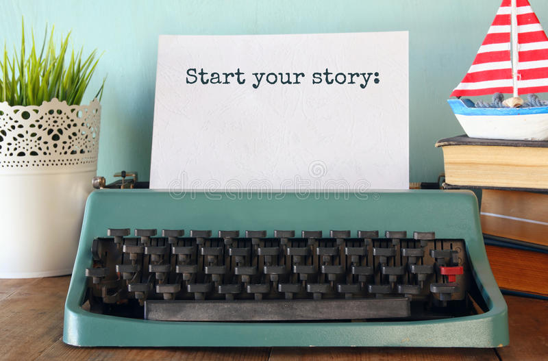 Vintage typewriter with phrase: START YOUR STORY. Photo of vintage typewriter with phrase: START YOUR STORY, on wooden table stock photo