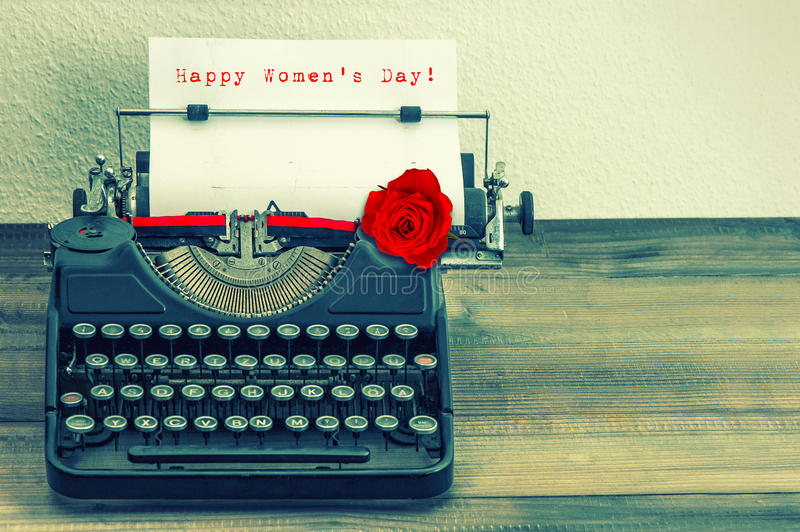 Vintage typewriter with red rose flower. Happy Womens Day stock photos