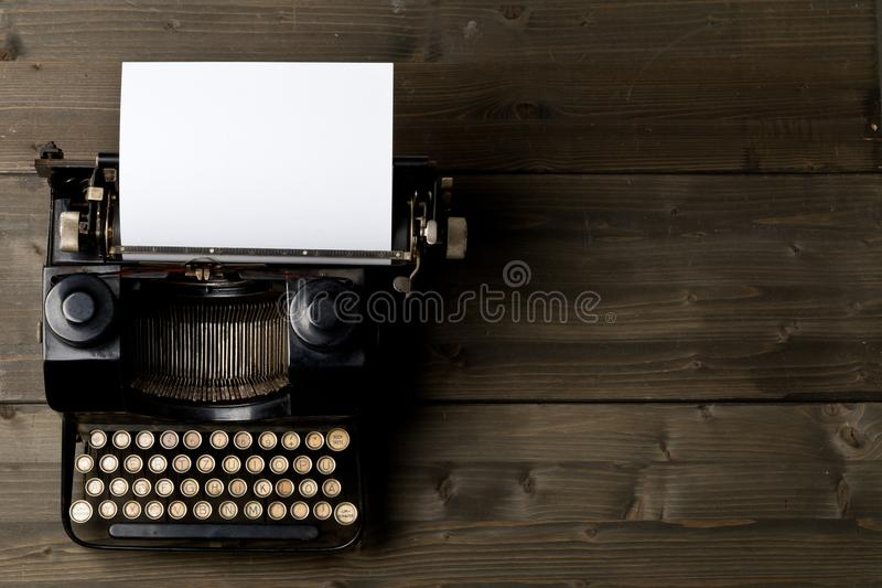 Vintage typewriter top down flatlay shot from above with empty,. Blank sheet of paper on wood table background stock photo