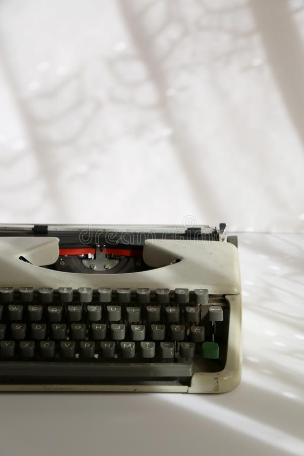 Vintage Typewriter. Illuminated by sunlight through lace curtains. Selective fous stock photography