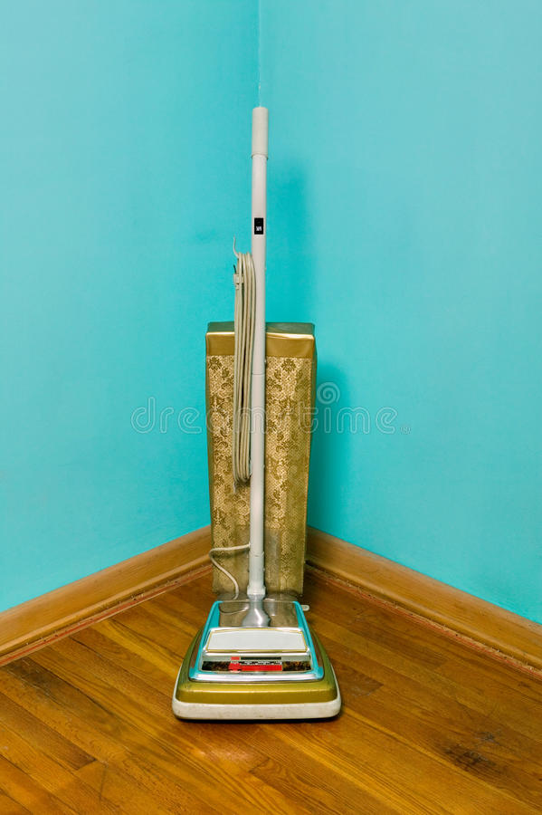 Vintage vacuum cleaner standing in room corner royalty free stock photos