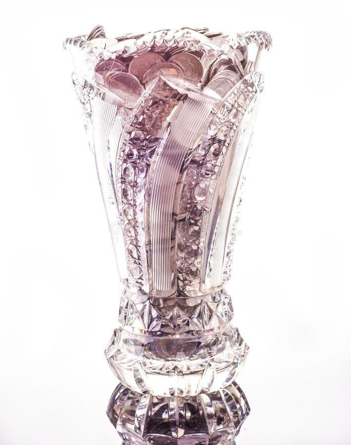 Vintage vase fulled coins. On white background royalty free stock photo