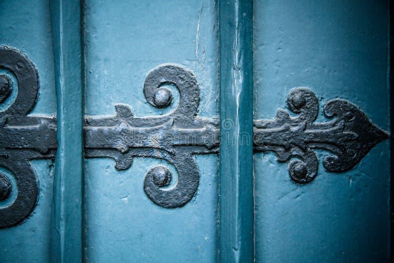 Vintage velho e seta preta oxidada do ornamento da porta do ferro na porta de madeira azul do estilo antigo pesado e maciço fotos de stock