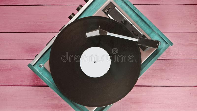 Vintage vinyl player on a blue wooden background. Top view. Retro media technologies. royalty free stock photo