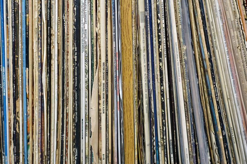 A Shelf of Vintage Vinyl Records. Vintage Vinyl Record Collection Stored on a Shelf Vertically with Spines Showing stock images