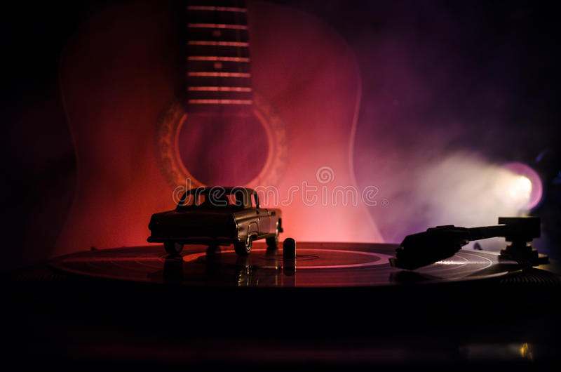 Vintage vinyl record playing on player and acoustic guitar on background with fire orange smoke. Blues concept. With Toy car stock photos