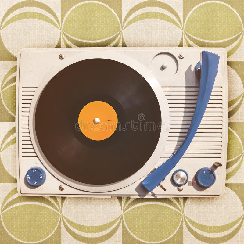Vintage vinyl turntable player on retro wallpaper royalty free stock photo