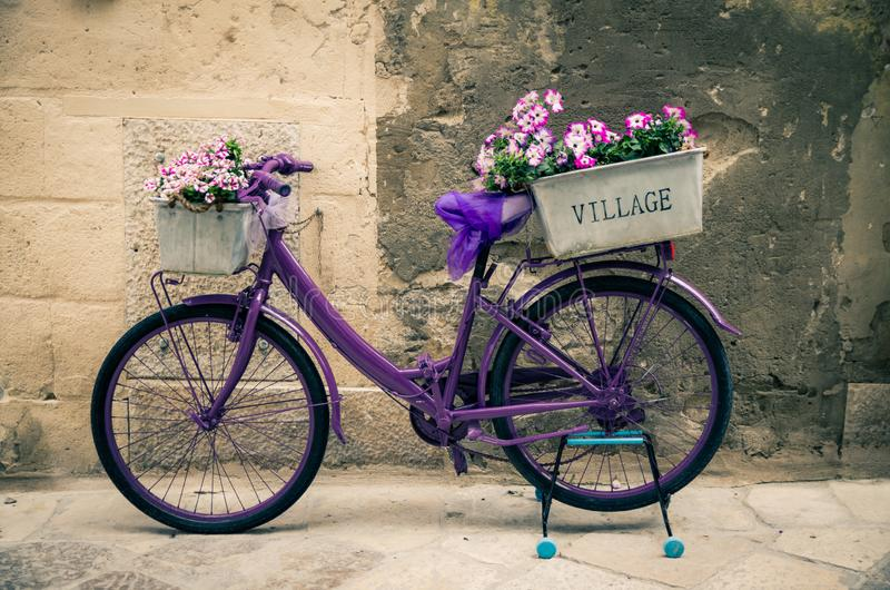 Vintage violet bike bicycle with box of flowers, Italy stock photos