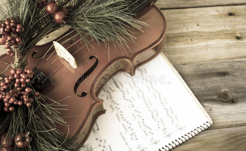 Vintage violin adorned with christmas fern lying on sheet music. Horizontal vintage layered image of a part of a violin adorned with christmas fern and royalty free stock photo