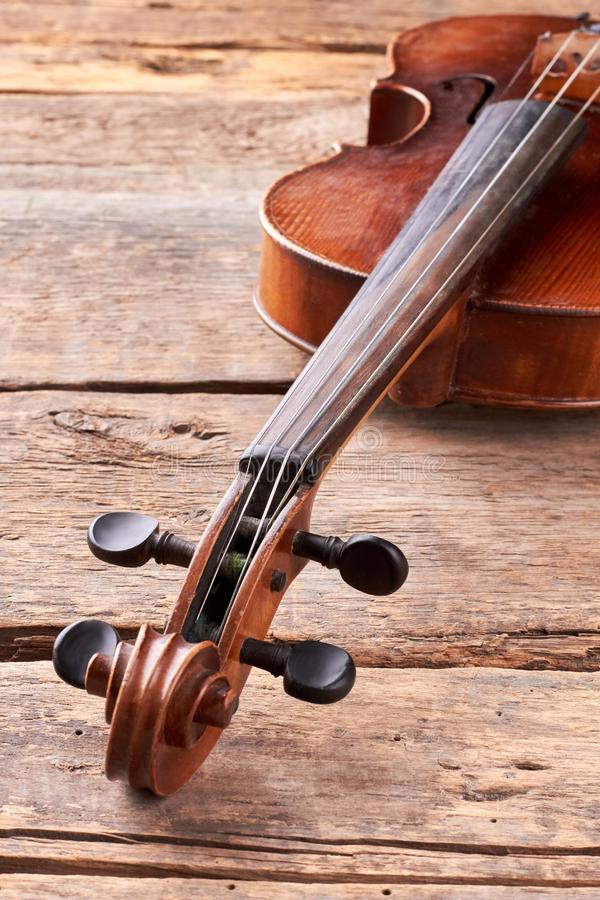 Vintage violin on wooden planks. Viola musical instrument on old wooden boards, vertical image. Cello close up of scroll and peg box. Classical instrument of royalty free stock images