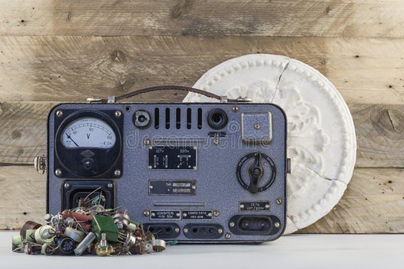 Vintage voltage regulator with transistors, resistors, radio parts and old plaster rosette wood backgraund. Vintage voltage regulator with transistors, resistors royalty free stock photos