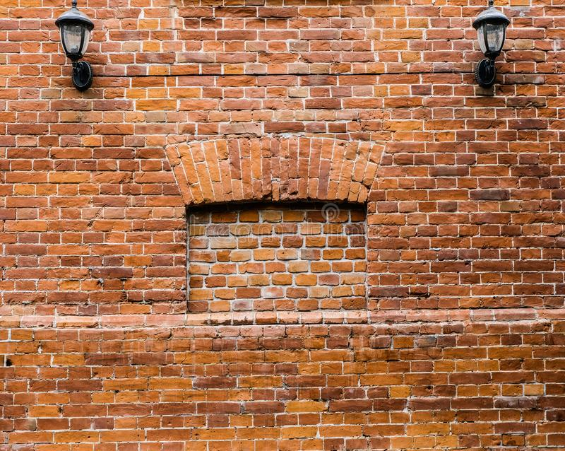 Vintage wall lamp on a red-orange and brown wall of old brick royalty free stock image