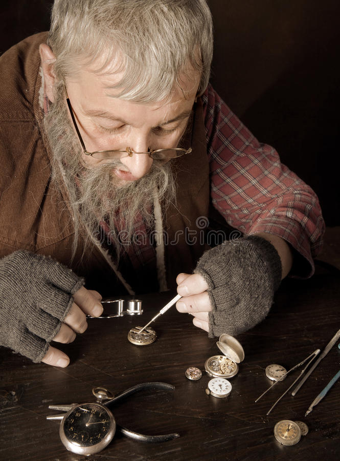 Vintage watch-maker. Old bearded man reparing antique watches using a magnifying glass royalty free stock images