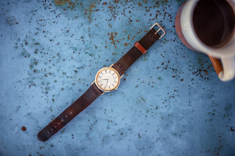Gold/silver vintage watch with leather bracelet. Gold/silver vintage wrist watch with brown leather bracelet on rustic blue metal bench suggesting the time is 07 stock photography