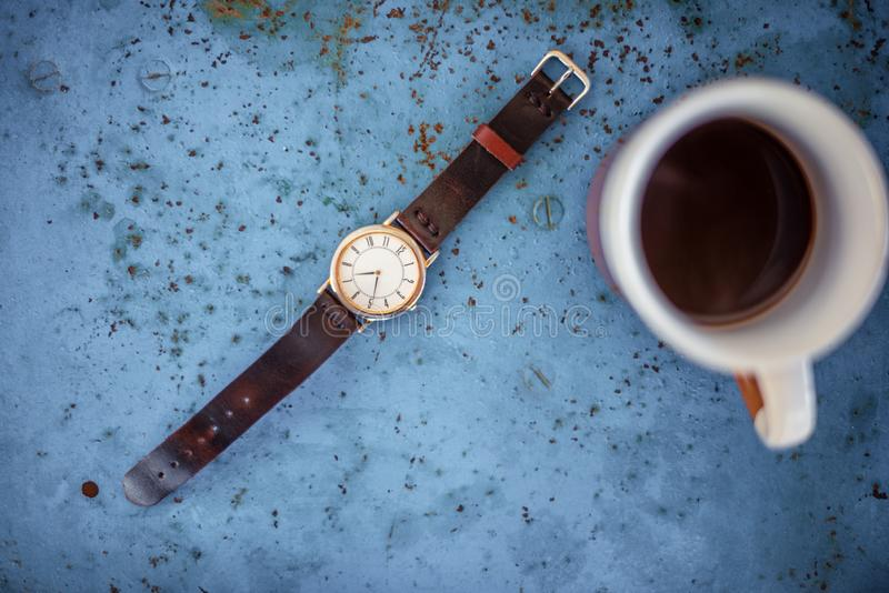 Gold/silver vintage wrist watch with brown leather bracelet. Gold/silver vintage wrist watch with brown leather bracelet on rustic blue metal bench suggesting royalty free stock images