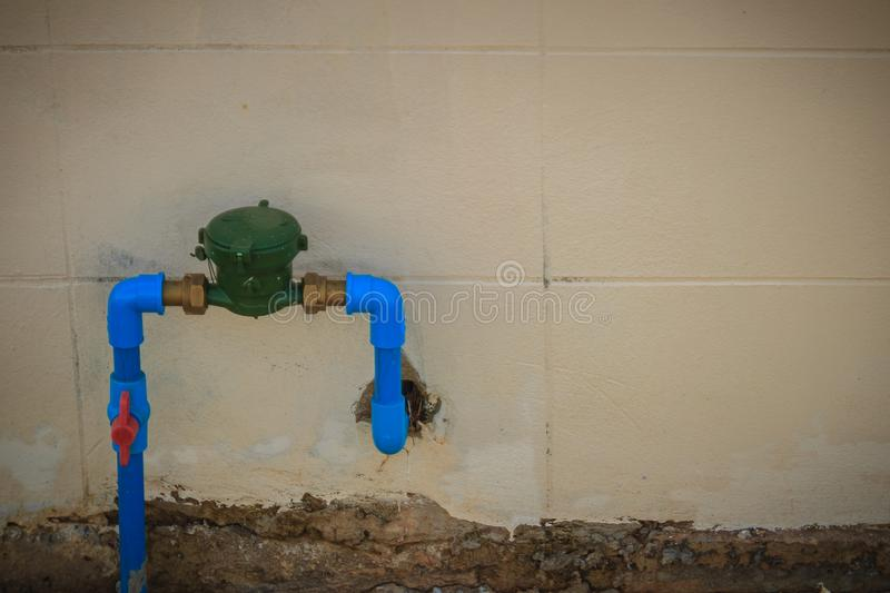 Vintage water meter installed with bronze joint, PVC elbow connector, blue PVC pipe and red water valve on the grungy wall. stock image