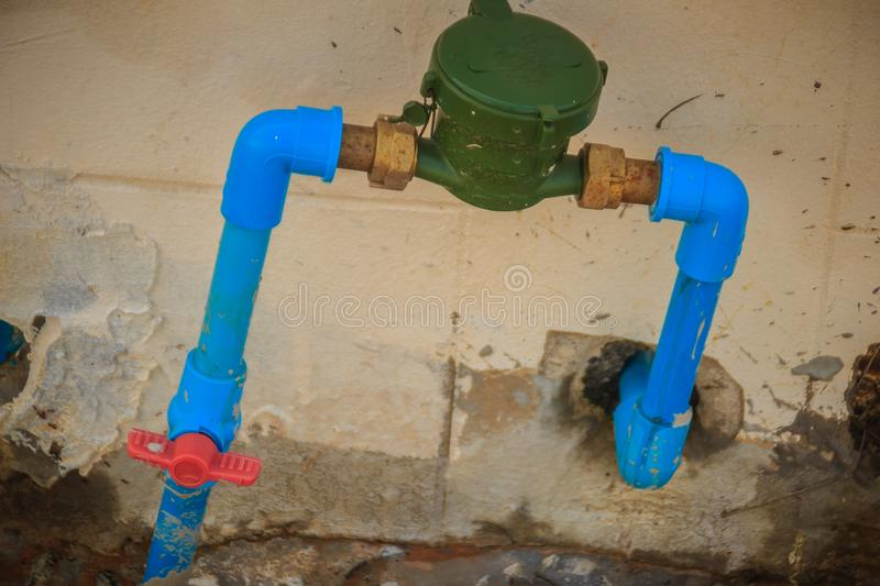 Vintage water meter installed with bronze joint, PVC elbow connector, blue PVC pipe and red water valve on the grungy wall. royalty free stock images