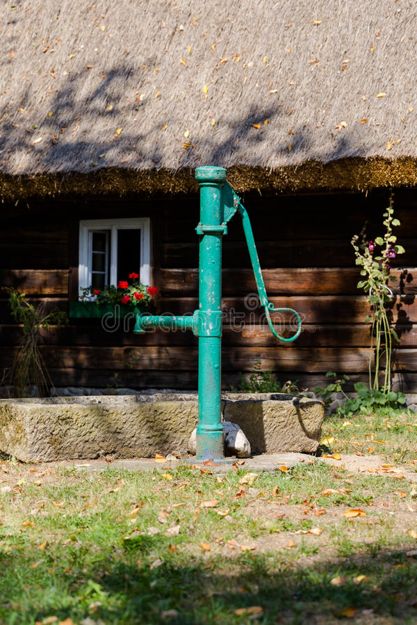 Vintage water pump on front of old wooden house. Vintage green water pump on front of the old wooden house royalty free stock photography