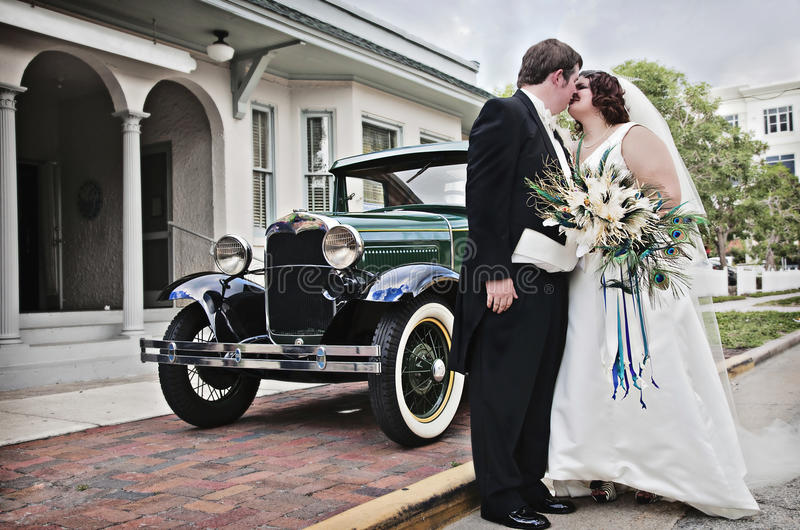 Vintage wedding. A bride and groom standing in front of an vintage car kissing