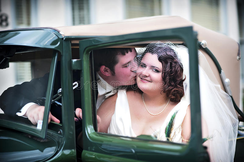 Vintage wedding couple. A groom kissing a vintage styled bride in a old antique car