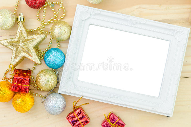 Vintage white blank photo frame with christmas decorations on wood background. stock photos
