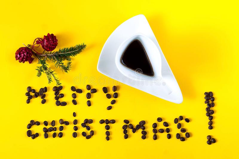 Vintage white ceramic cup with coffee and Inscription of merry Christmas, laid out from the beans of coffee. Creative yellow background-color of the year 2019 stock images
