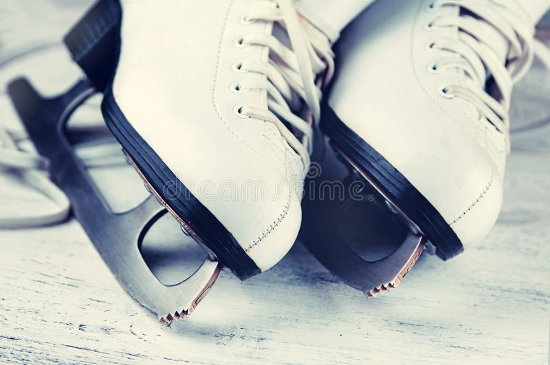 Vintage white female skates for figure skating, on a light wooden background. royalty free stock photos