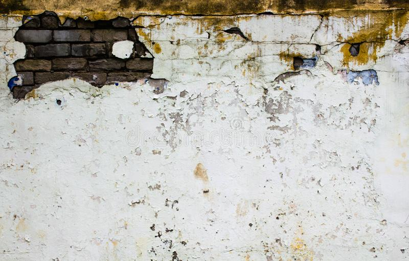 Vintage white wall with sprinkled white plaster and red brick background texture. Old brick wall with peeling plaster, grunge stock photo