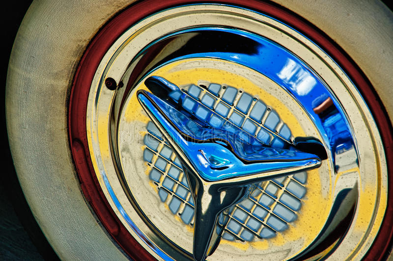 Vintage White Wall Tire and Chrome Hubcap. Vintage cracked white wall tire and chrome waffle hubcap with colors and blurs royalty free stock images