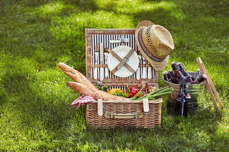Vintage wicker picnic hamper with beers in cooler. Vintage wicker picnic hamper filled with fresh vegetarian food and French baguettes beside a silver wine royalty free stock photography