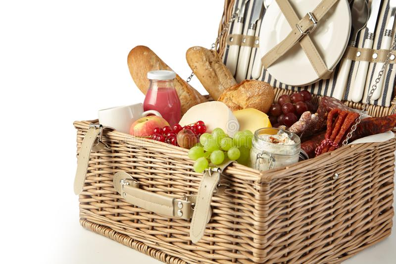 Vintage wicker picnic hamper filled with food. Including fresh fruit, assorted cheeses, spicy sausages, baguette and juice isolated on white in a cropped view stock photo