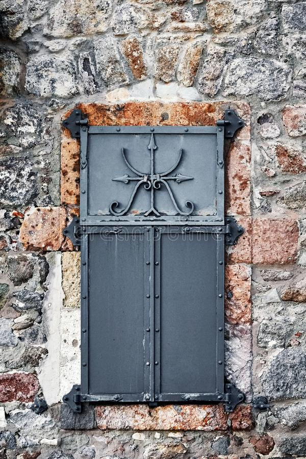 Vintage window with black iron shutter and stone wall royalty free stock photo