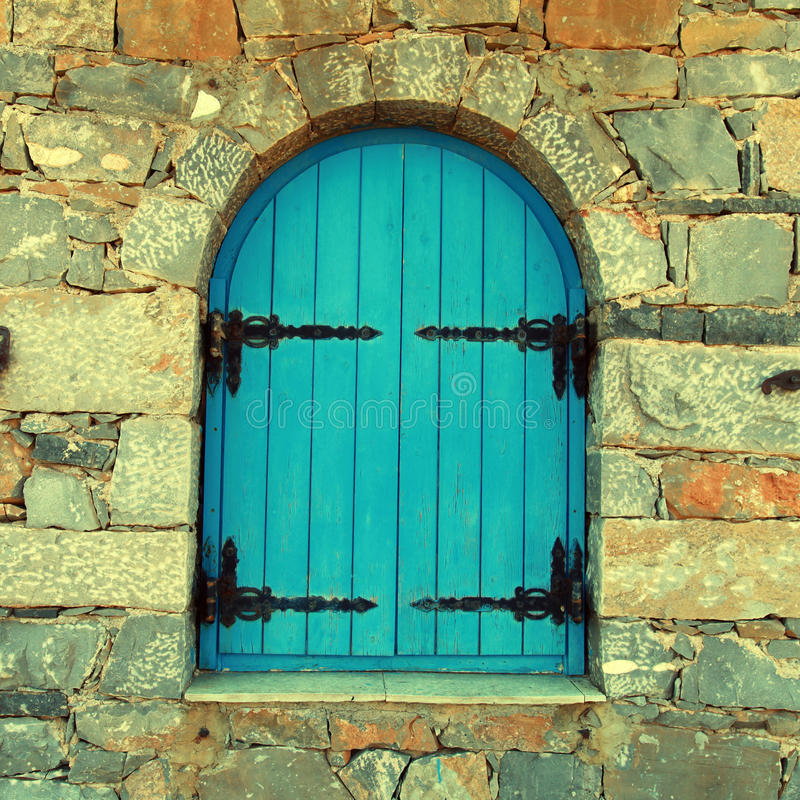 Vintage window with blue close shutters, Crete, Greece. Vintage window with blue close shutters in old stone wall, Crete, Greece. instagram effect, square image royalty free stock photography