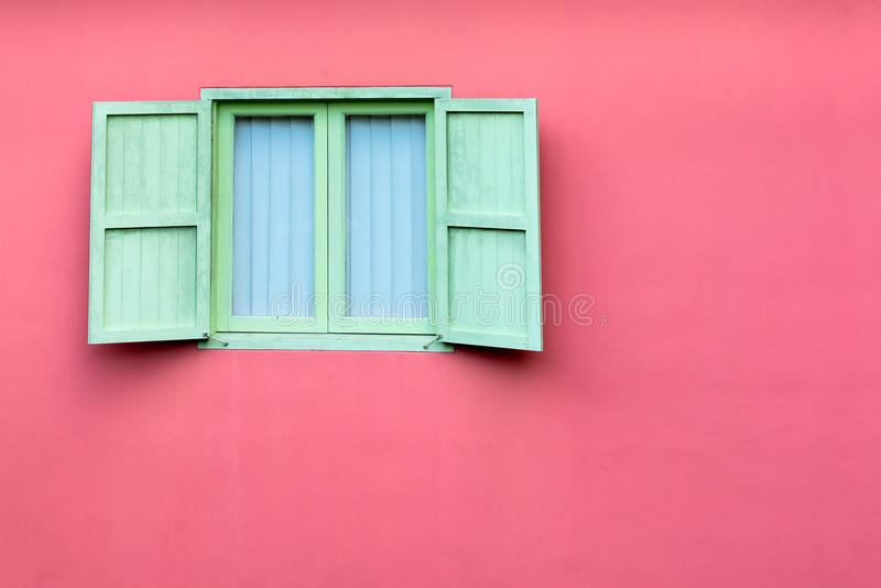 Vintage window with green shutters on pink wall royalty free stock images