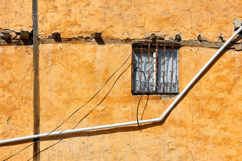 Vintage window with wrought iron grate and a water pipe on old weathered facade of a house stock image