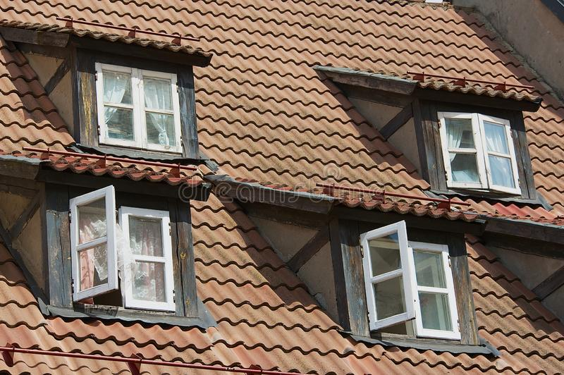 Vintage windows at the attic roof with brown tiles in the historical part of Riga, Latvia. stock image