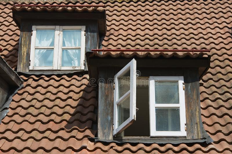 Vintage windows at the attic roof with brown tiles in the historical part of Riga, Latvia. stock photos