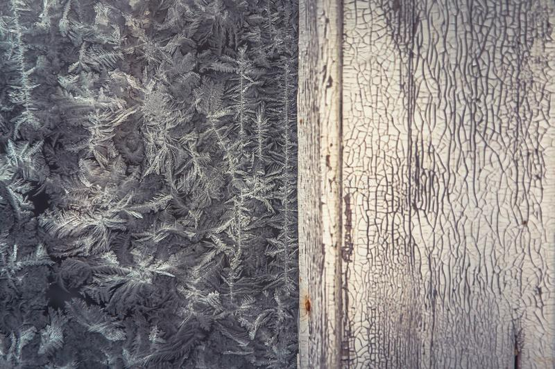 Vintage winter frost background with old wooden bleached surface with frost pattern on frozen window as Christmas background. Vintage winter frost background royalty free stock images