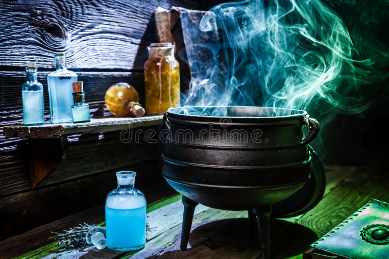 Vintage witcher cauldron with blue smoke and potions for Halloween stock photography