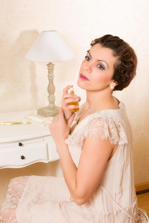 Vintage woman with perfume. Beautiful vintage 1920s woman applying perfume in her boudoir stock photo