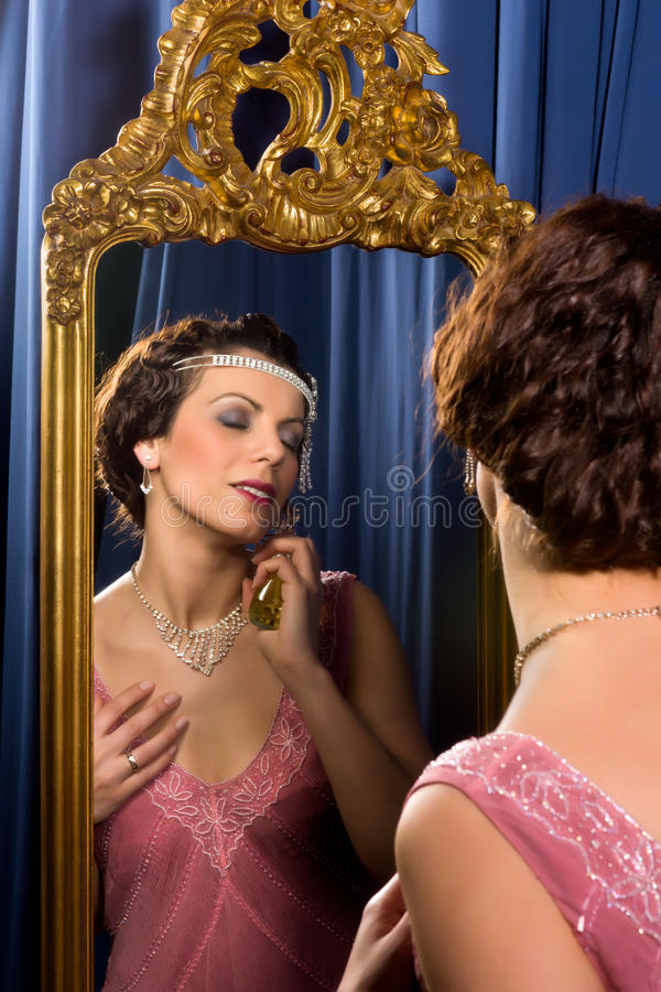 Vintage woman with perfume. Stunning vintage 1920s woman looking in an antique mirror stock image